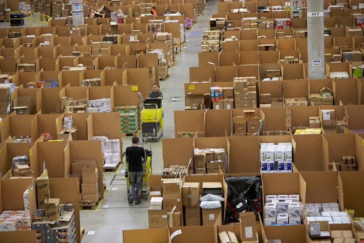 Kuva valtavasta salista, joka on täynnä laatikoita. Kaksi työntekijää työntää kärryjä salin halki kulkevalla käytävällä.