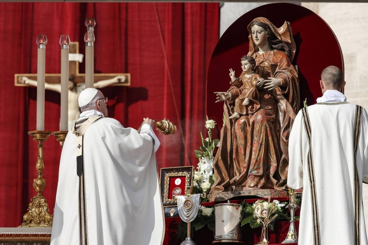 Paavi heiluttaa suitsukeastiaa Neitsyt Mariaa ja Jeesus-lasta esittävän patsaan edessä. Taustalla on punainen seinäkangas, jonka edessä on krusifiksi.