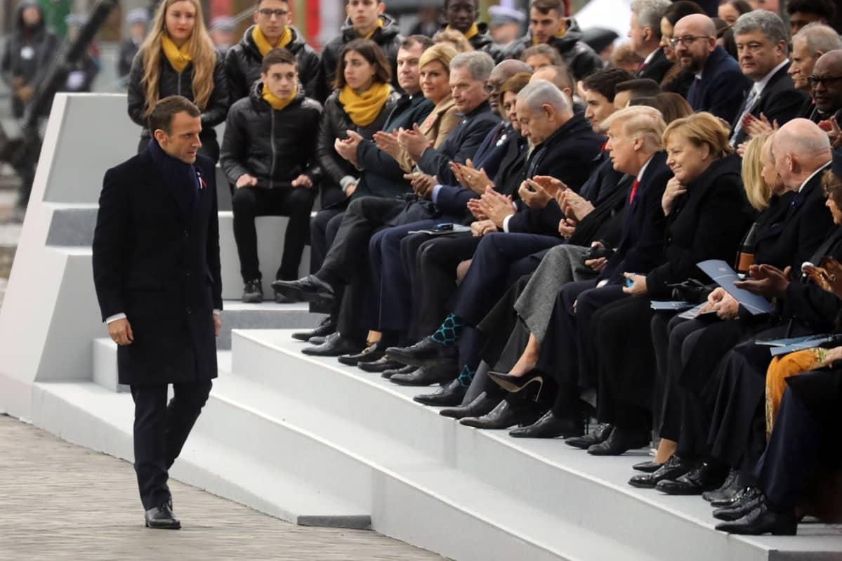 Kuvassa Macron kävelee istumassa olevien valtiojohtajien edestä. Istumassa muun muassa Merkel, Trump ja Niinistö.
