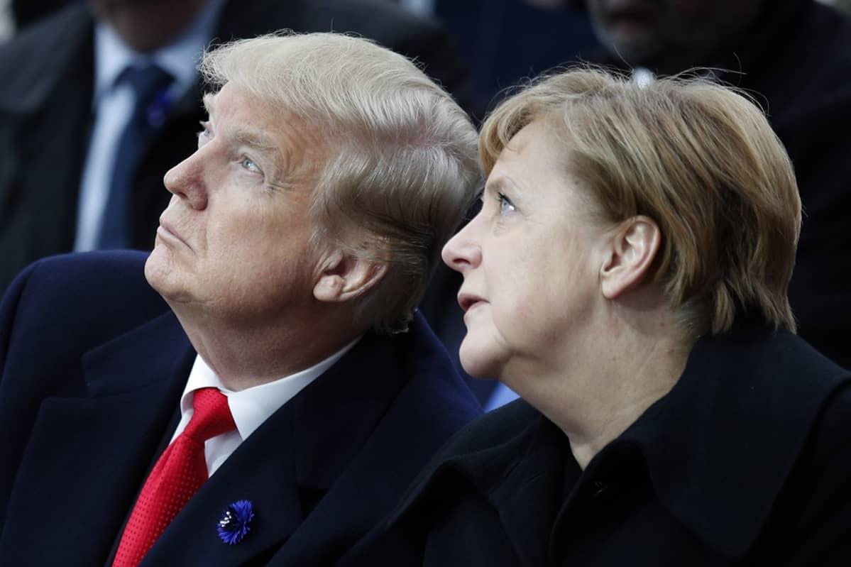 Kuvassa Donald Trump ja Angela Merkel istumassa vierekkäin. Molemmat katsovat yläviistoon.