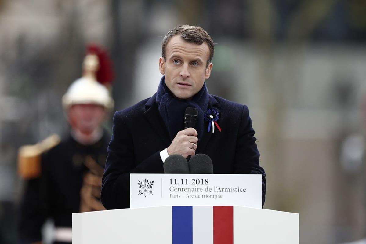 Emmanuel Macron puhujanpöntön takana. Hänellä on kädessään mikrofoni. Puhujanpöntössä on Ranskan lippu.