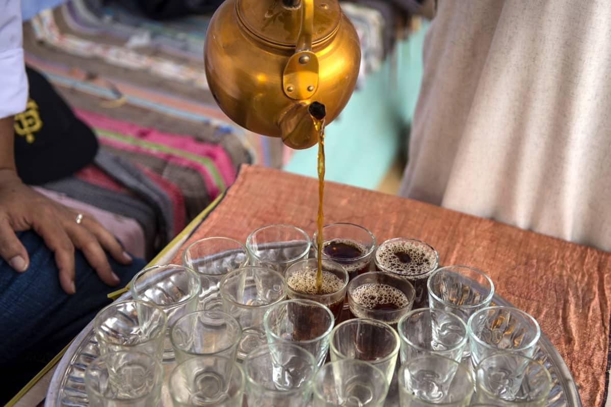 Kuparipannusta kaadetaan teetä tarjottimella oleviin laseihin.