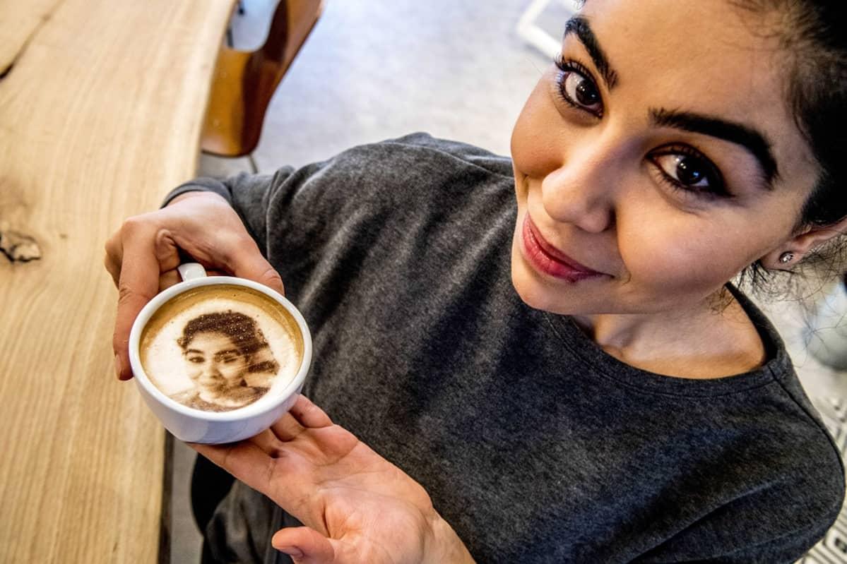 Nainen pitelee kuppia, jonka kahvin kintaan on muotoiltu vaahdosta hänen selfie-kuvansa.