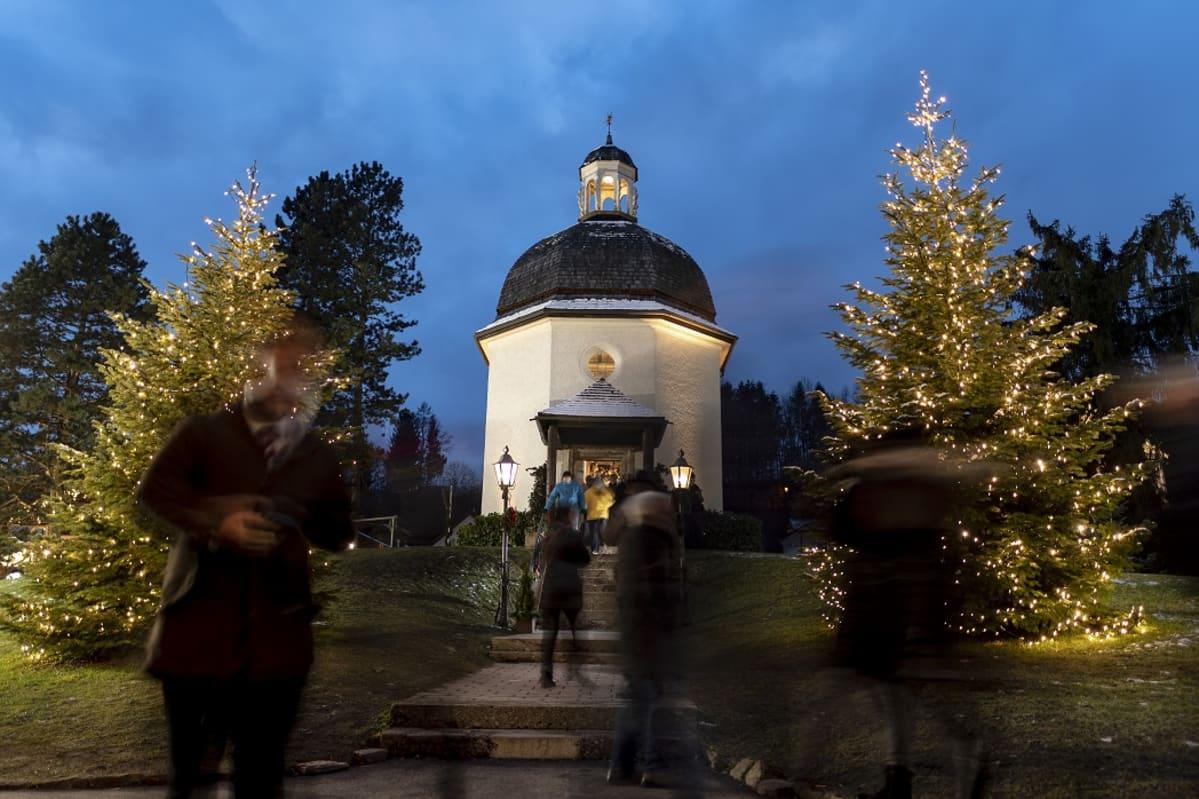 Kaksi valaistua joulukuusta sininen taivasta ja valkoinen kappeli.
