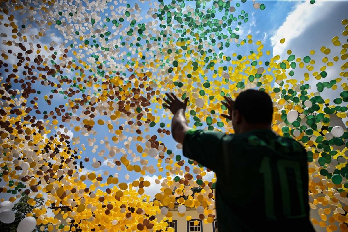 Mies ojentaa käsiään kohti taivaalle kohoavaa Brasilian lipun väristen ilmapallojen suurta parvea.