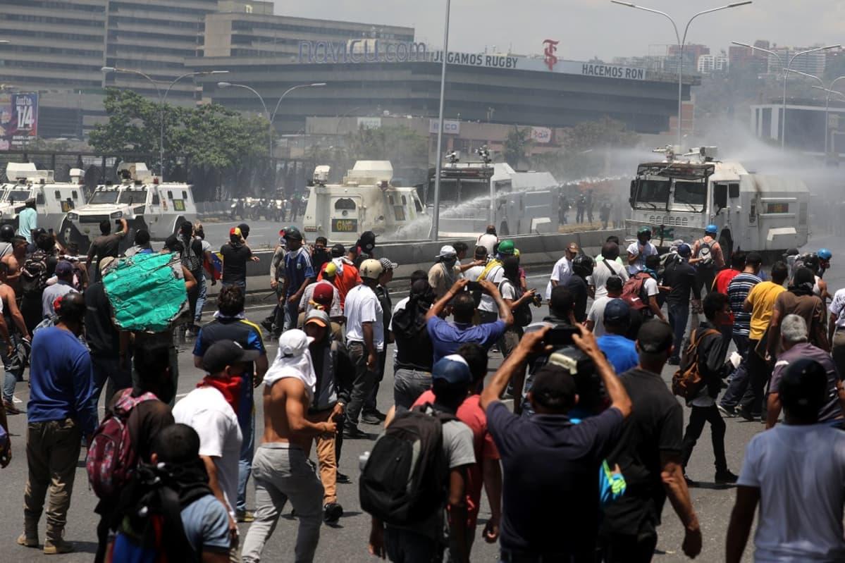 Kuvassa vesitykeillä ammutaan vettä mielenosoittajien päälle.