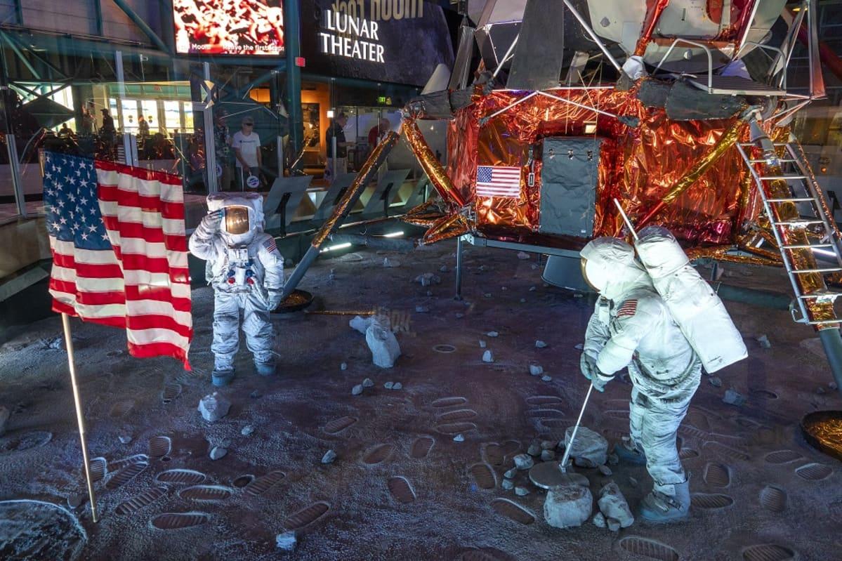 Luonnollisen kokoinen kopio kuumoduulista, kahdesta astronautista ja Yhdysvaltain lipusta teatterin edustalla.