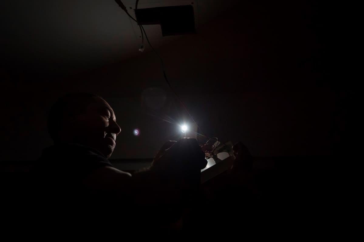 Toimistotyöläinen jatkoi työtään sähkökatkon aikana Caracasissa.
