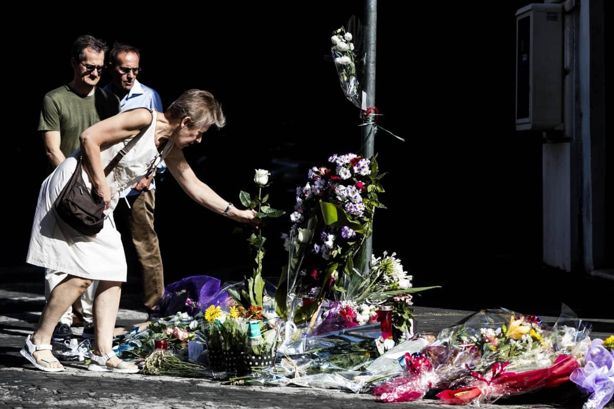 Nainen laskee kukkia murhapaikalle.