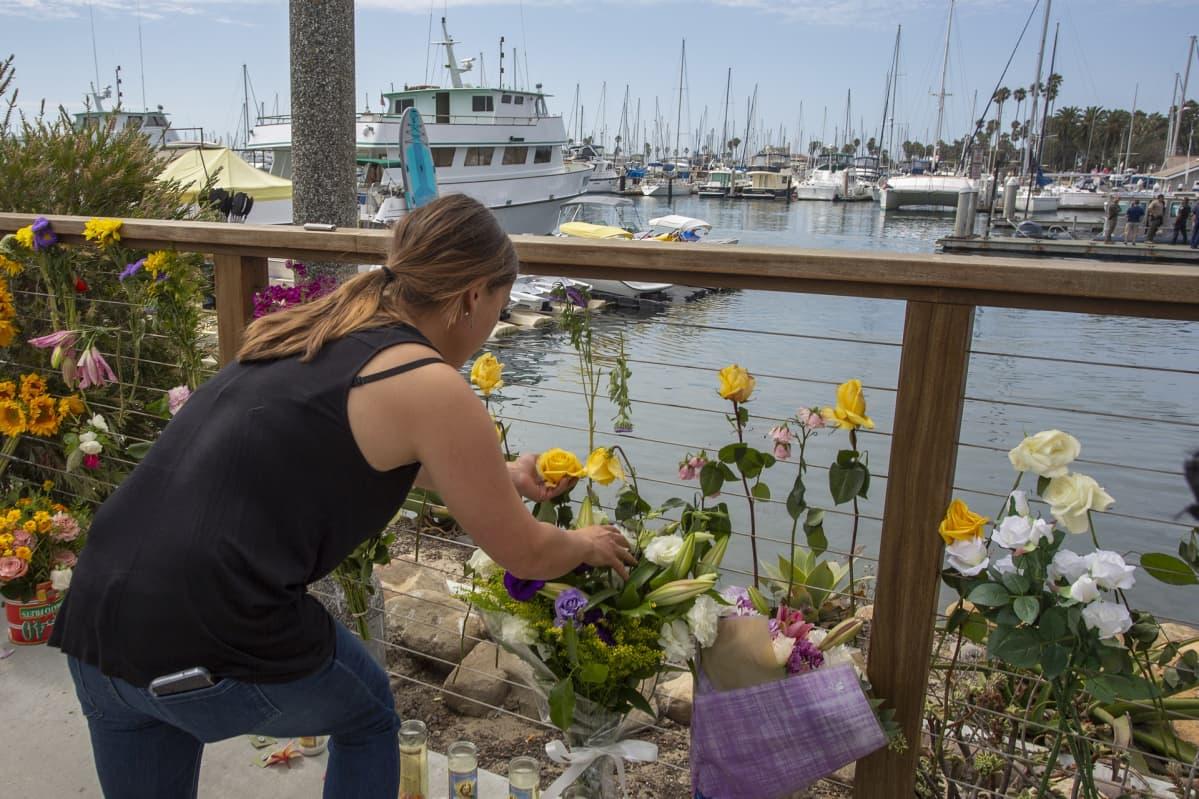 Nainen laskee kukkia satamassa.