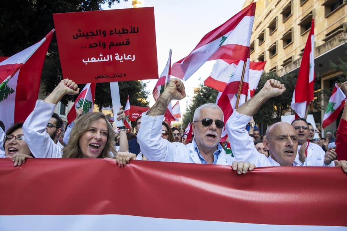 Etualalla kolme mielenosoittajaa punaisen lakanan takana. Heillä kaikilla on oikea käsi nyrkissä ja ylhäällä. Taustalla heilutetaan Libanonin lippuja.