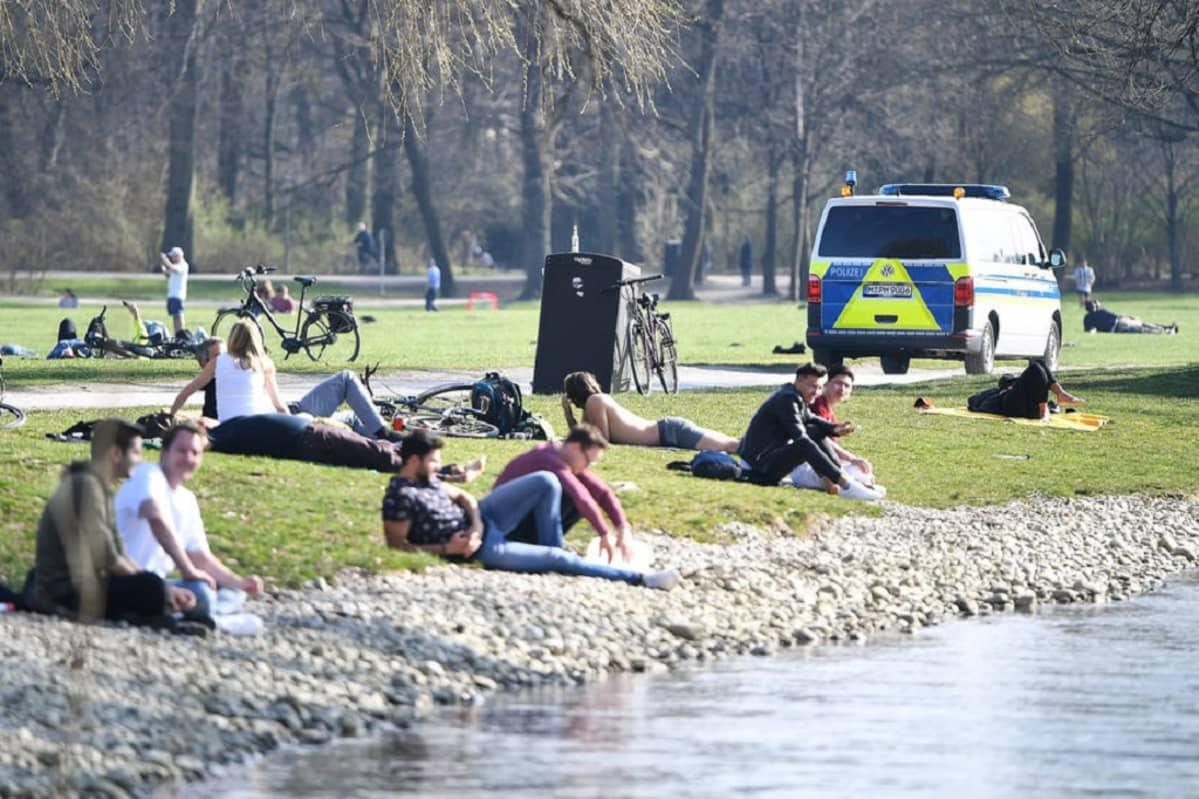 Kuvassa ihmisiä istumassa puistossa veden äärellä. Taustalla ohi ajava poliisiauto.
