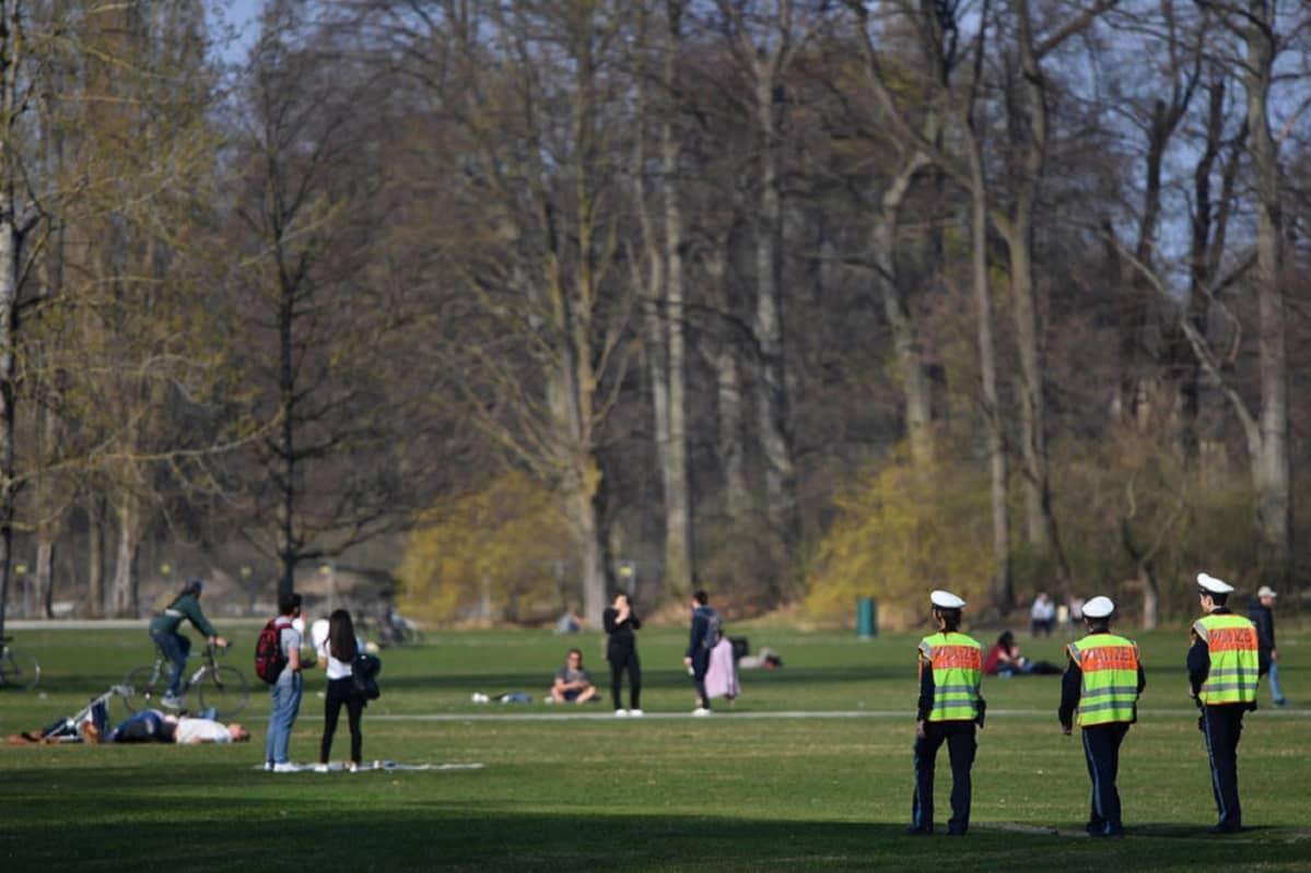 Taustalla ihmisiä puistossa. Etualalla kolme poliisia.
