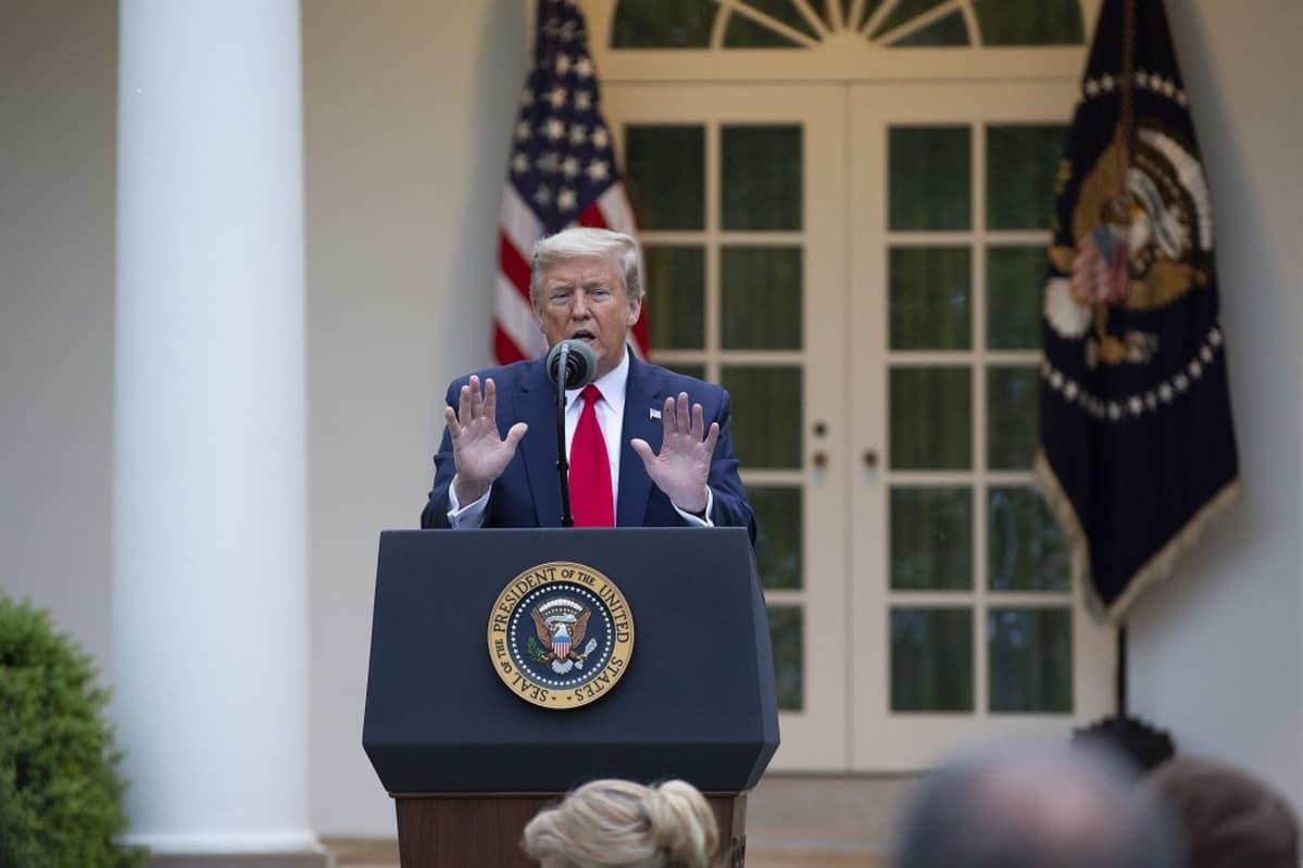 Kuvassa Donald Trump puhujanpöntön takana. Taustalla Yhdysvaltain lippu.