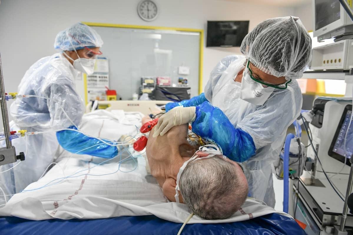 Kaksi suojavarusteisiin pukeutunutta hoitajaa auttaa vanhaa miestä, joka makaa lavitsalla.