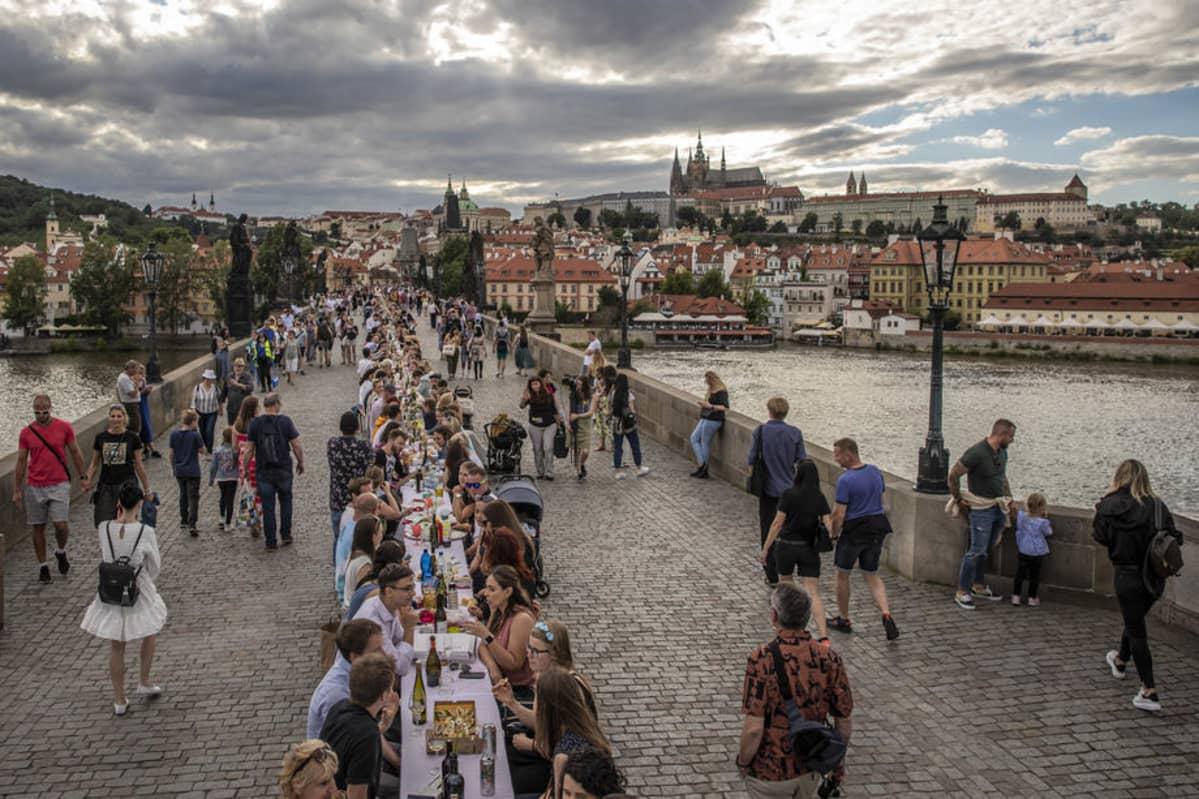 Ihmisiä juhlii Kaarlen sillalla Prahan keskustassa.