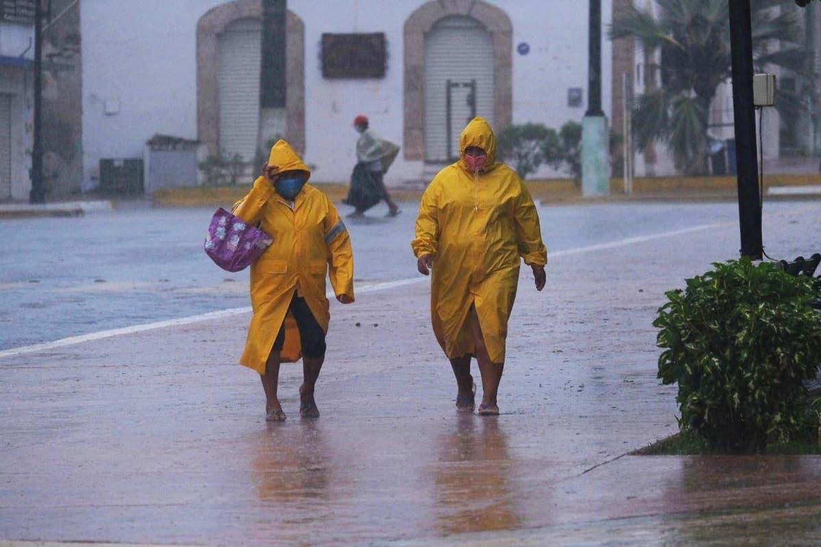 Ihmisiä kadulla vesisateessa Tiziminissä Meksikossa.