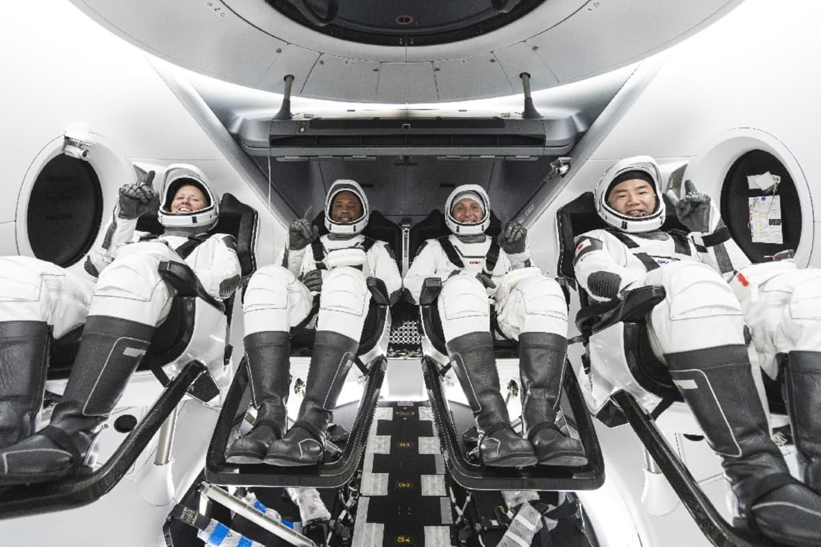 Neljä astronauttia avaruuspuvuissa istumassa aluksessaan.