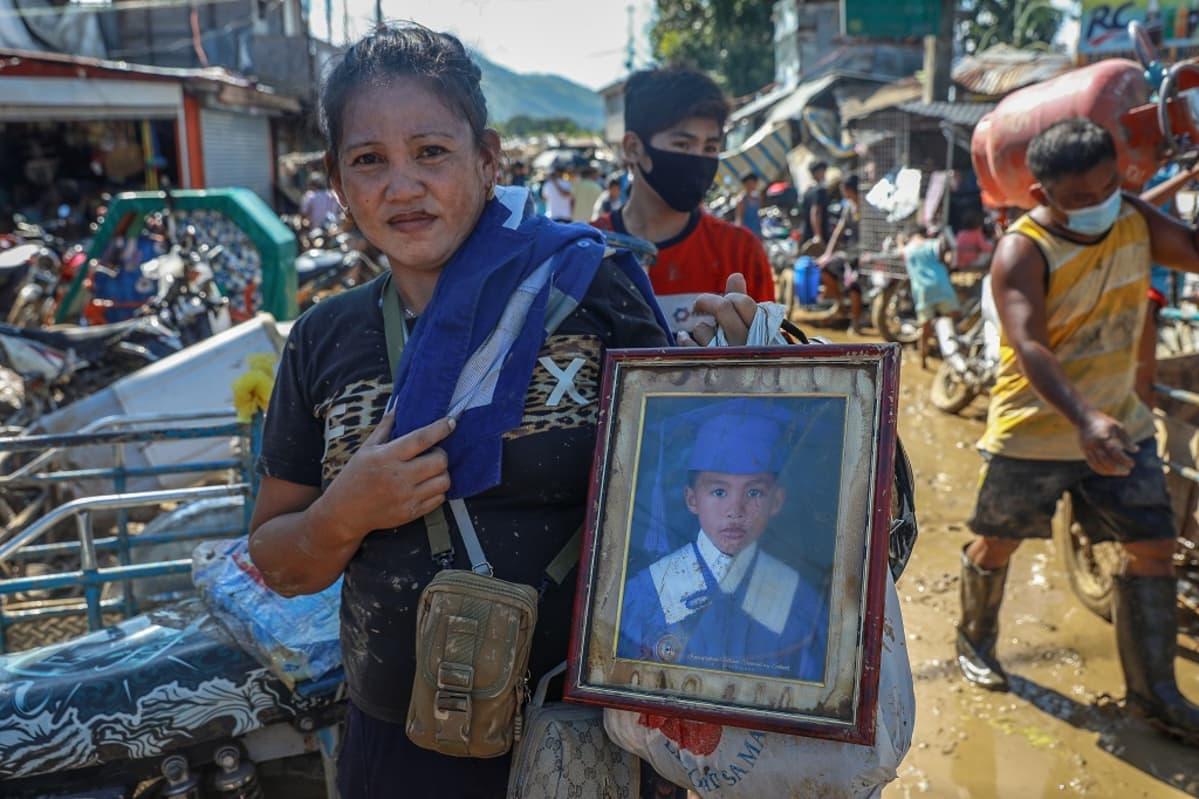 Nainen pitää poikansa kuvaa kädessään.