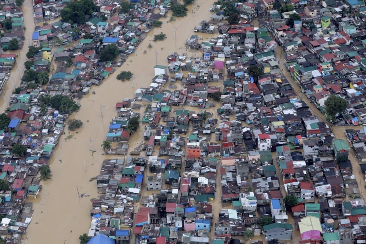 Tulvaveden saartamia hökkelitaloja ja taloja.