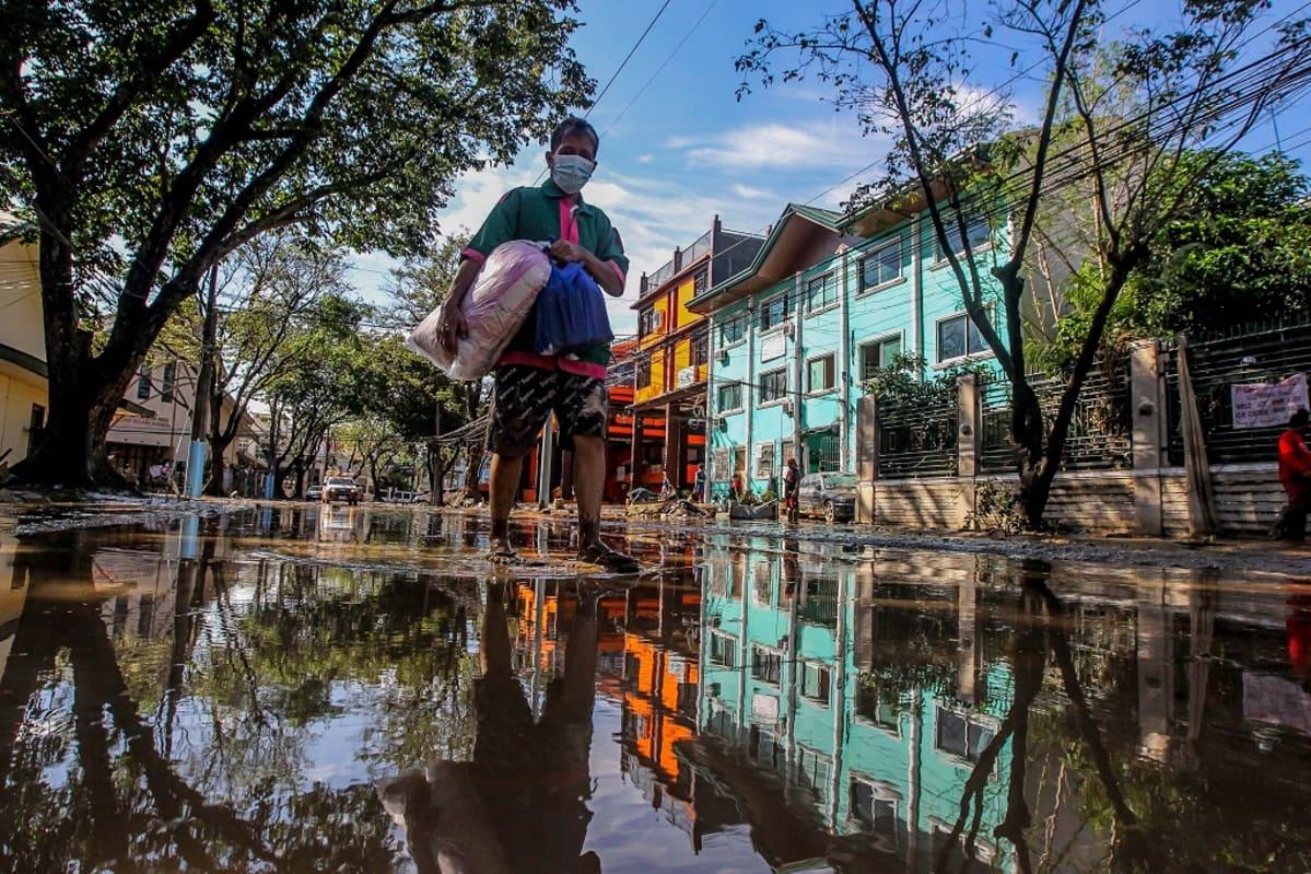 Mies seisoo veden peittämällä kadulla. Talojen julkisivut heijastuvat veteen.