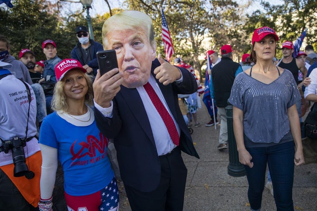 Trumpia puolustava mielenosoittaja otti itsestään selfien naamari päässä Washingtonissa lauantaina.