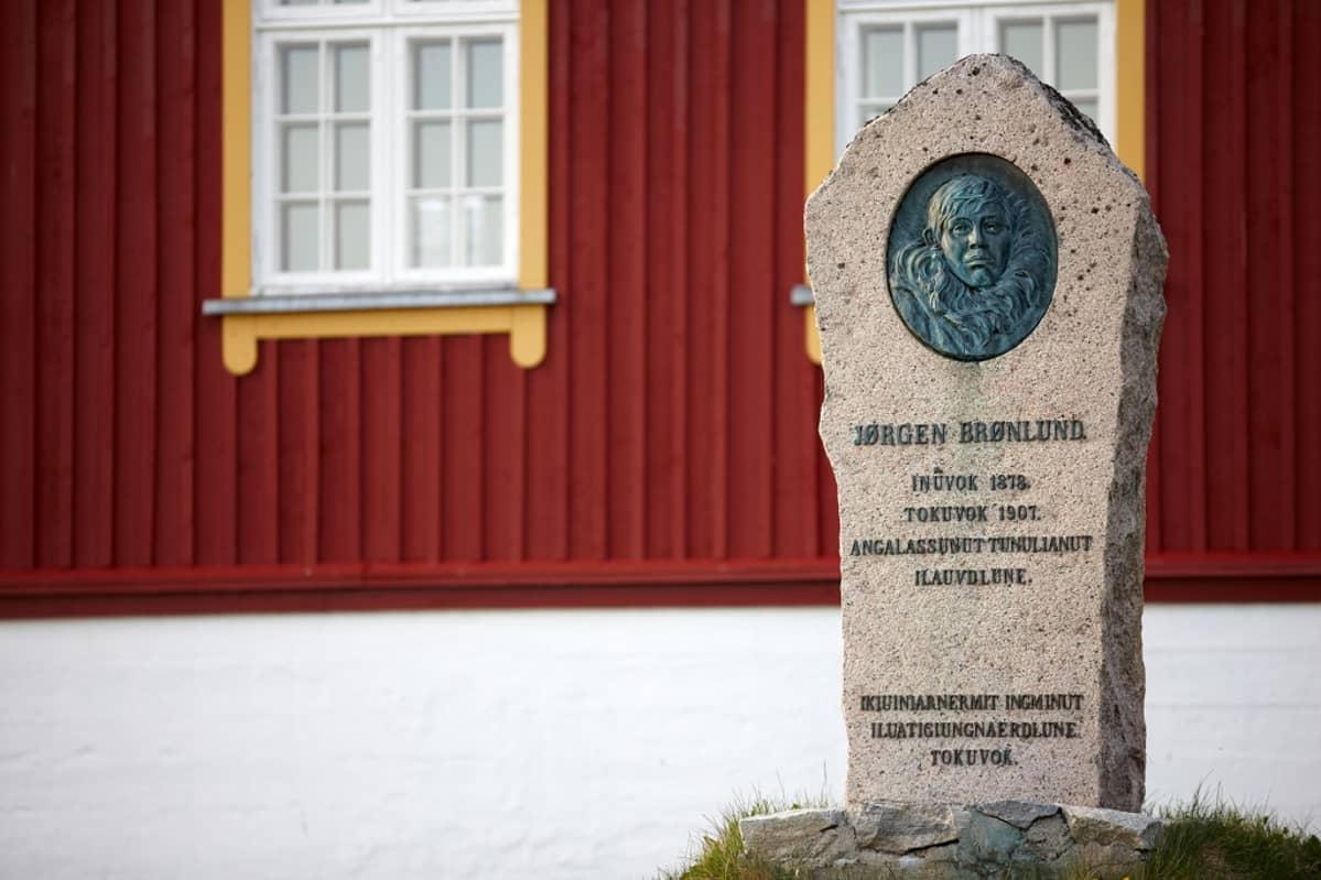 Muistokivi punaisen puurakennuksen edessä. Kivessä on Jørgen Brønlundin kasvokuva ja synnyin- ja kuolinpaikat ja -vuodet: Inuvok 1878, Tokuvok 1907.