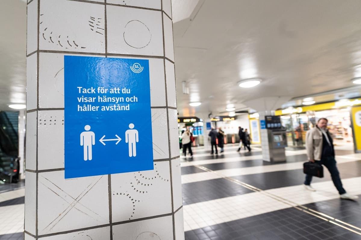 Metroaseman pylvääseen on liimattu kyltti, jossa lukee: Tack för att du visar hänsyn och håller avstånd