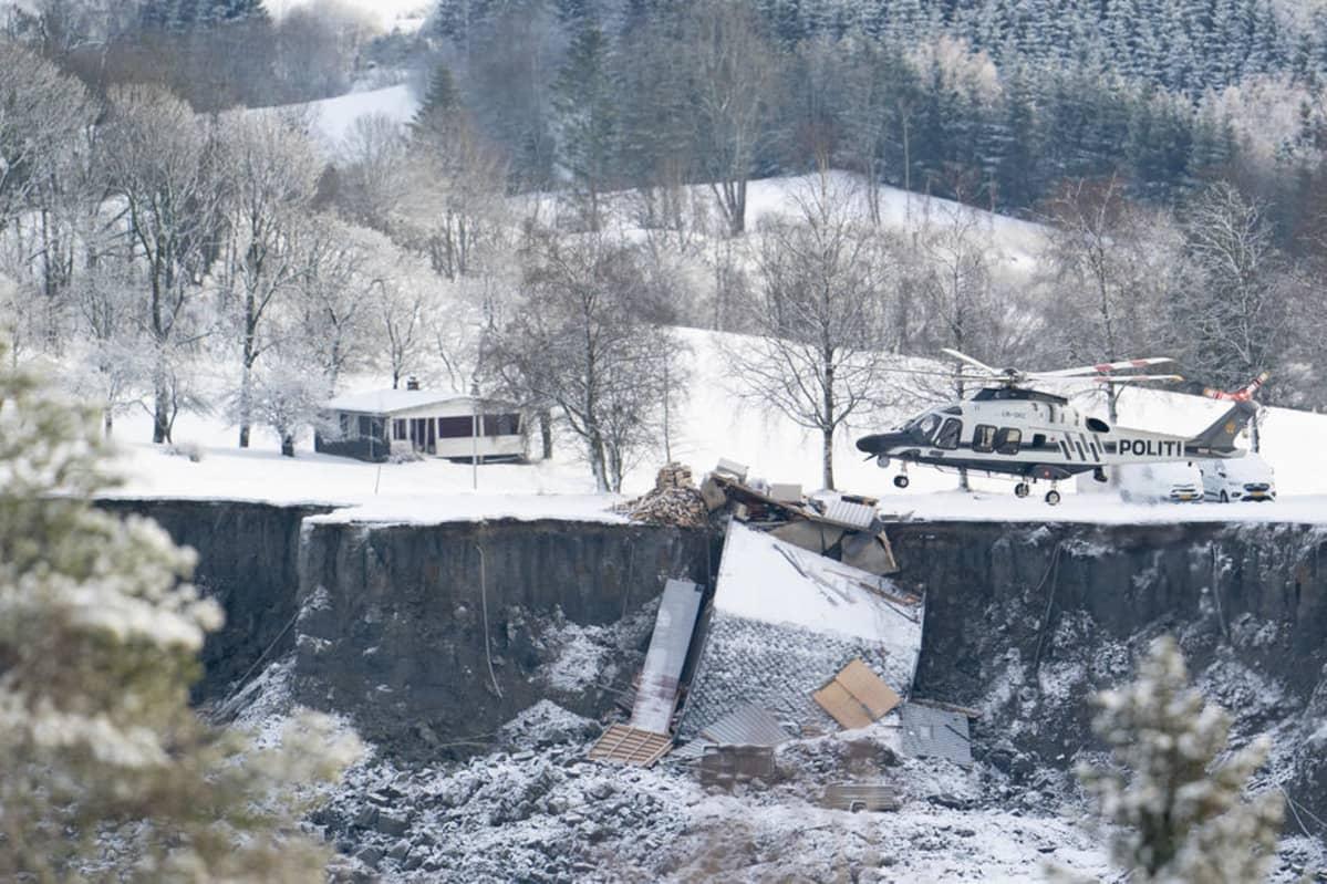 Helikopteri lentää tuhoutuneen talon ohi.