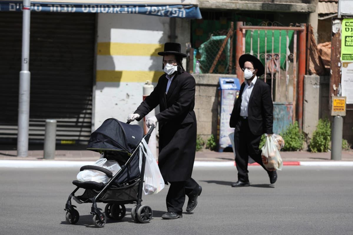 Suojamaskeihin pukeutuneita ultraortodoksisia miehiä Bnei Brakissa, Israelissa