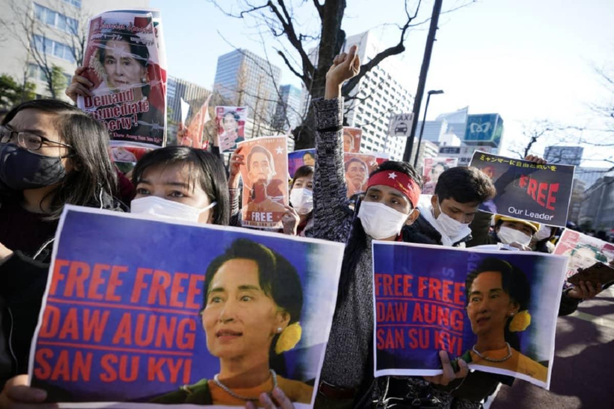 Kuvassa on mielenosoittajia, joilla on käsissään kylttejä, joissa vaaditaan Aung San Suu Kyin vapauttamista.