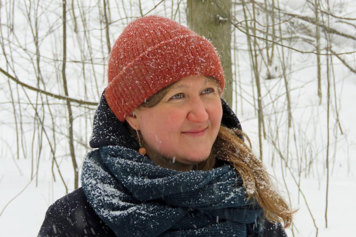Anna Haukka lumisateisessa metsässä