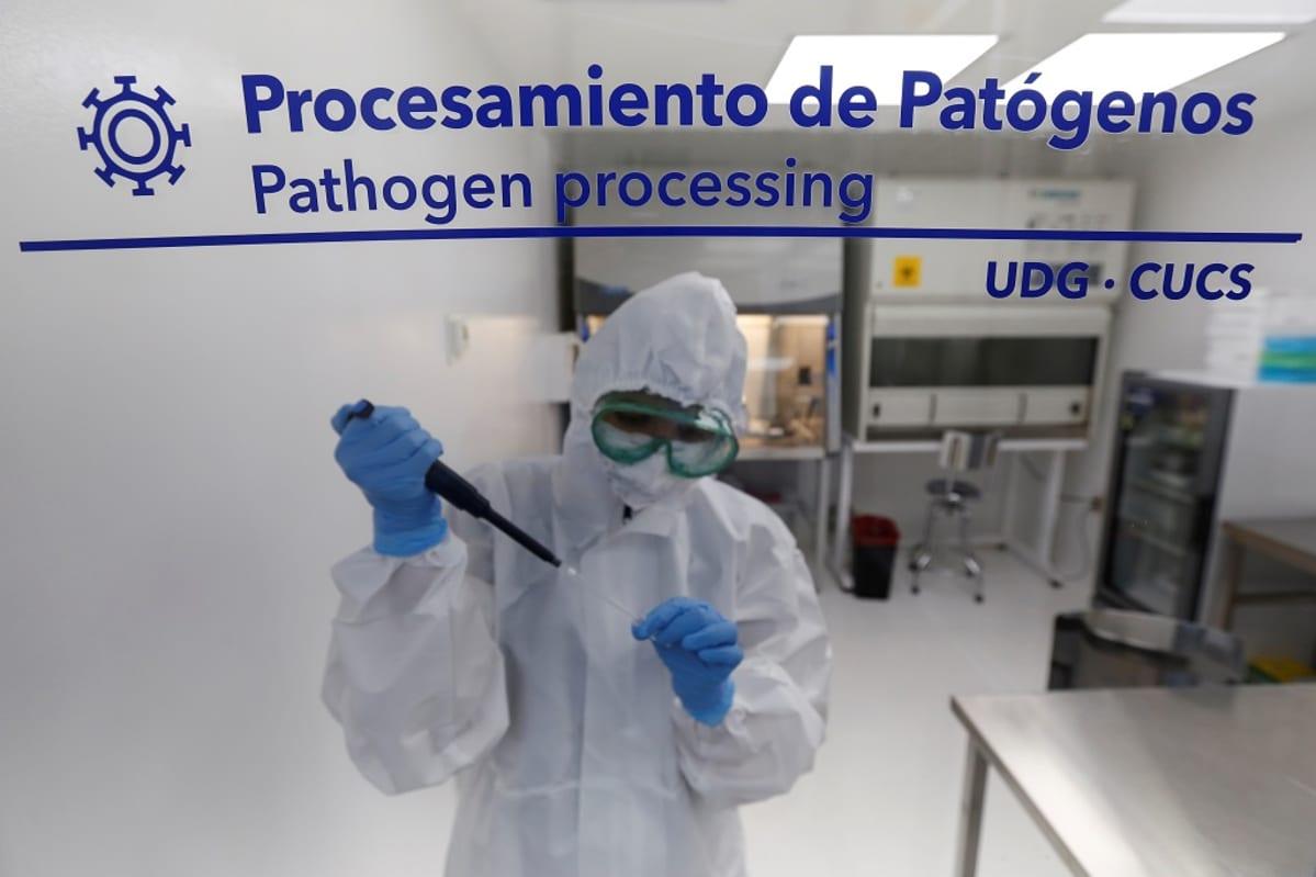 Laboratorion ikkunan läpi otettu kuva suojapukuisesta tutkijasta.