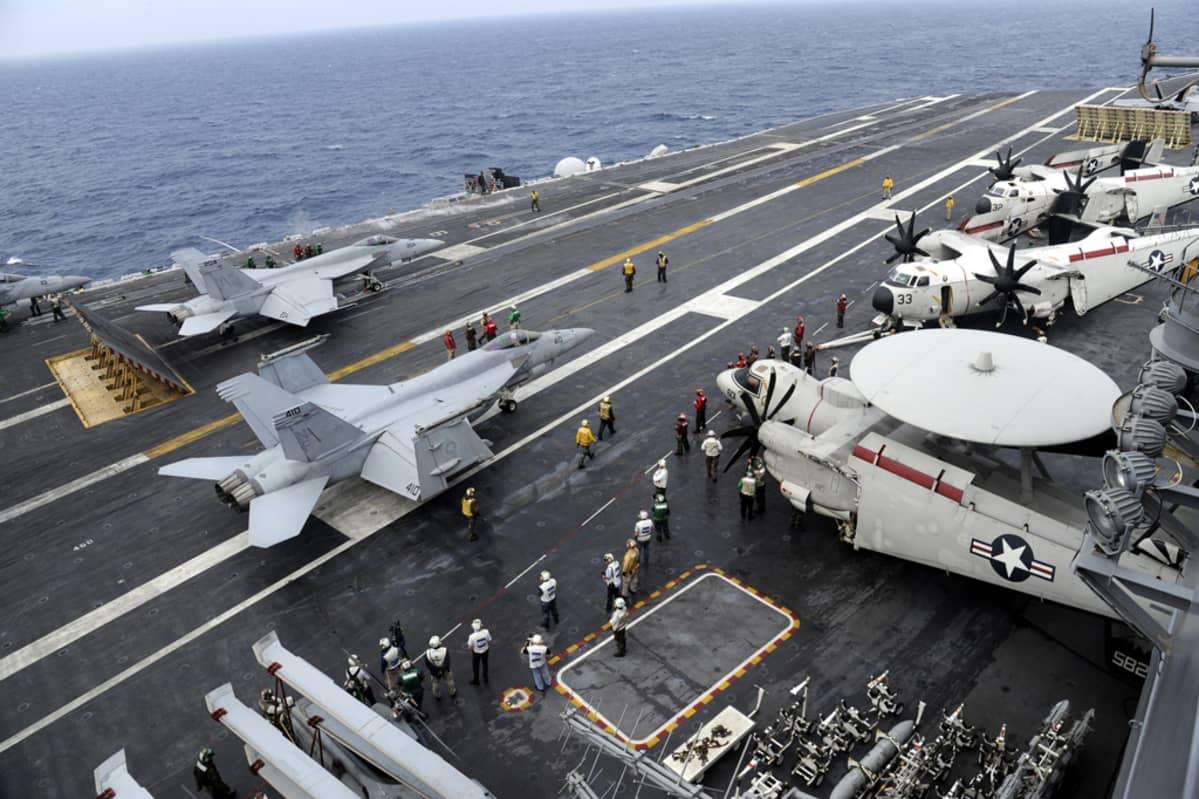 Lentotukialus USS George Washingtonin kannella helikoptereita ja hävittäjiä.