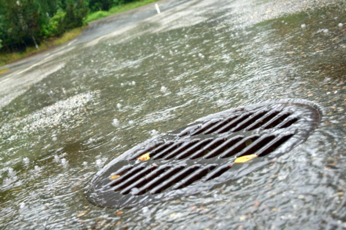 Vettä valuu viemäriin sateella.