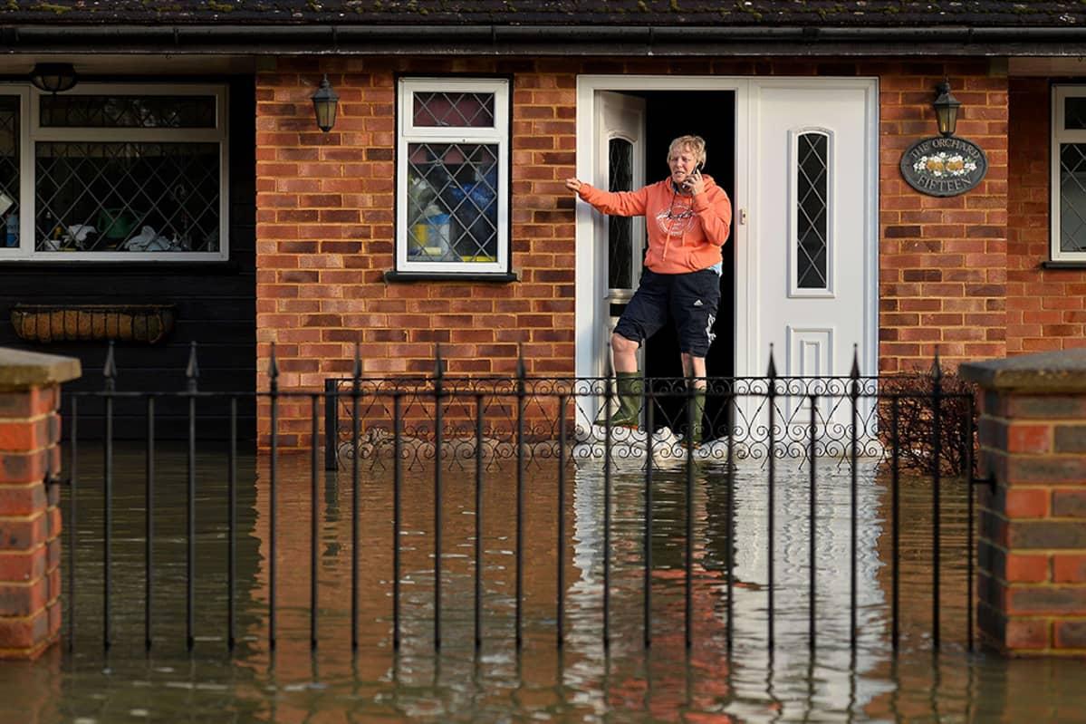 Nainen ovella tulvaveden ympäröimässä talossa.