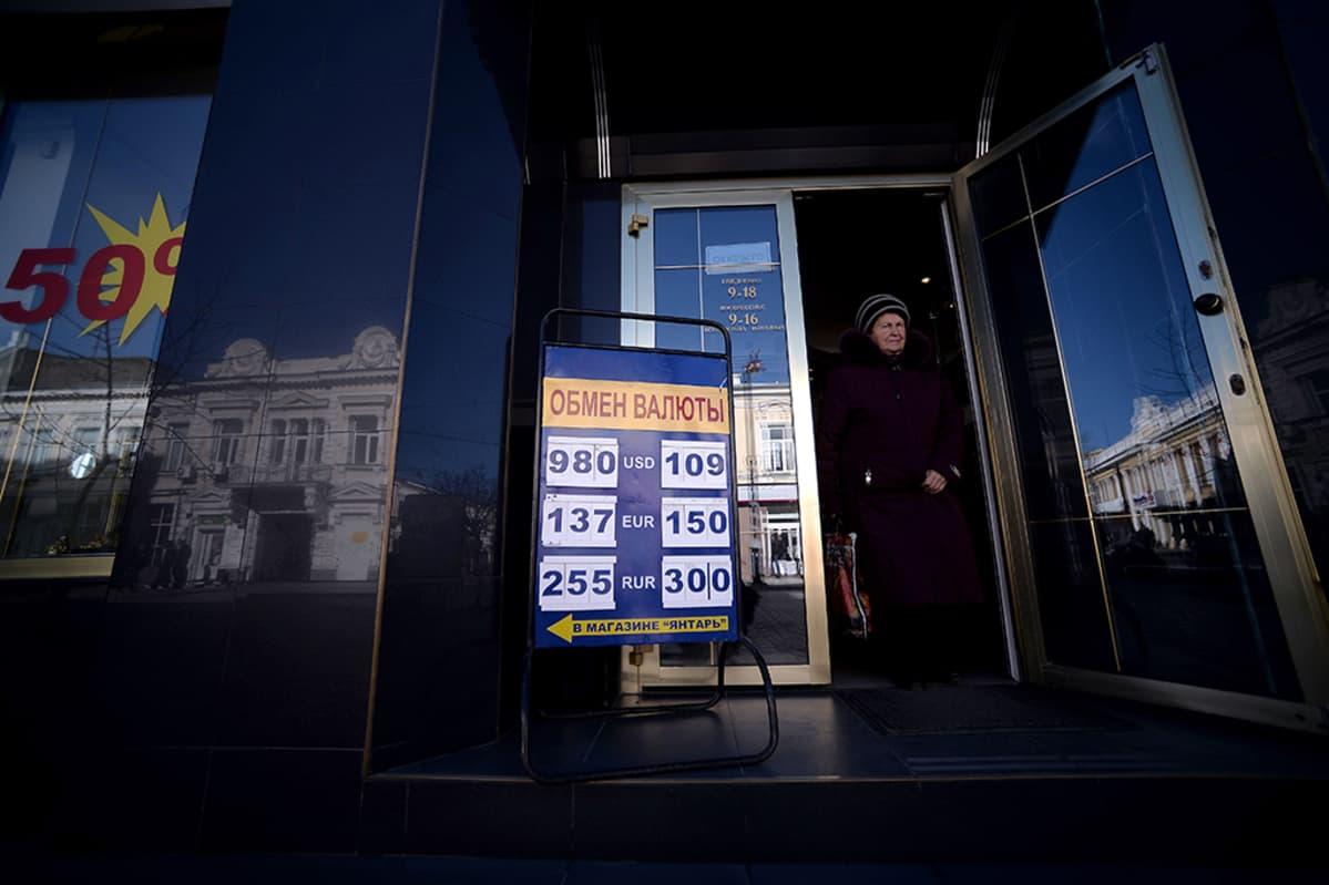 Nainen astuu ulos valuutanvaihtotoimistosta Simferopolissa 17. maaliskuuta 2014.