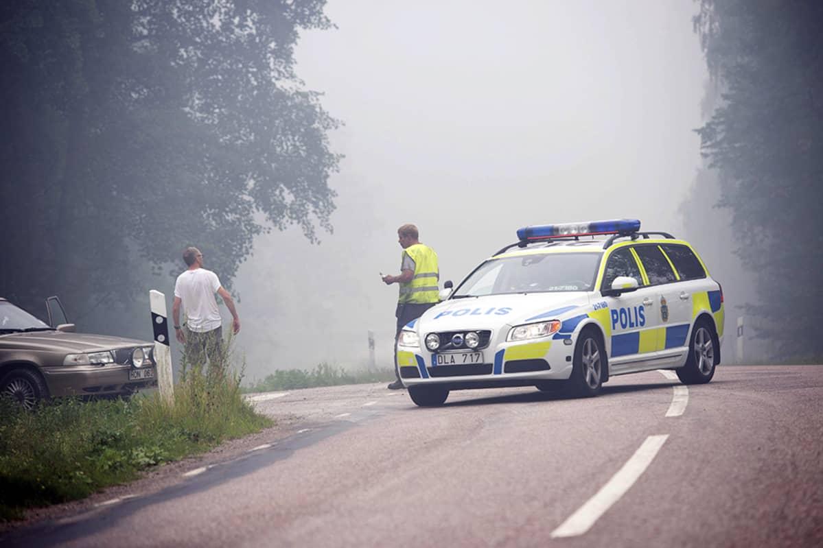 poliisiauto savuisella tiellä. Poliisi ja paikallinen mies keskustelevat.