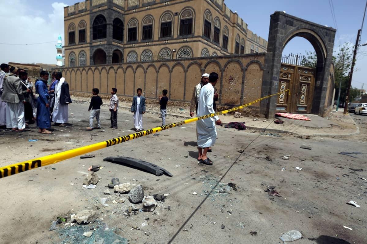 Ihmisiä pommin runteleman moskeijan edessä. Rikospaikka on eristetty poliisin keltaisella muovinauhalla.