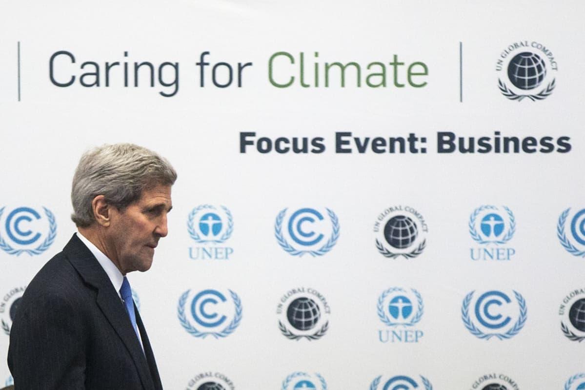 """Yhdysvaltain ulkoministeri on kuvan vasemmassa laidassa tummassa puvussa, sininen kravatti kaulassaan. Taustalla on seinätaulu, jossa on tekstiä: """"Caring for Climate. Focus Event: Business."""""""