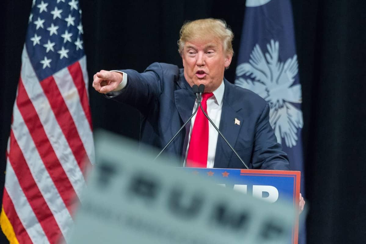 Donald Trump puhuu ja osoittaa oikealla kädellään jonnekin kuvaajasta takavasemmalle. Taustalla näkyy Yhdysvaltain lippu.