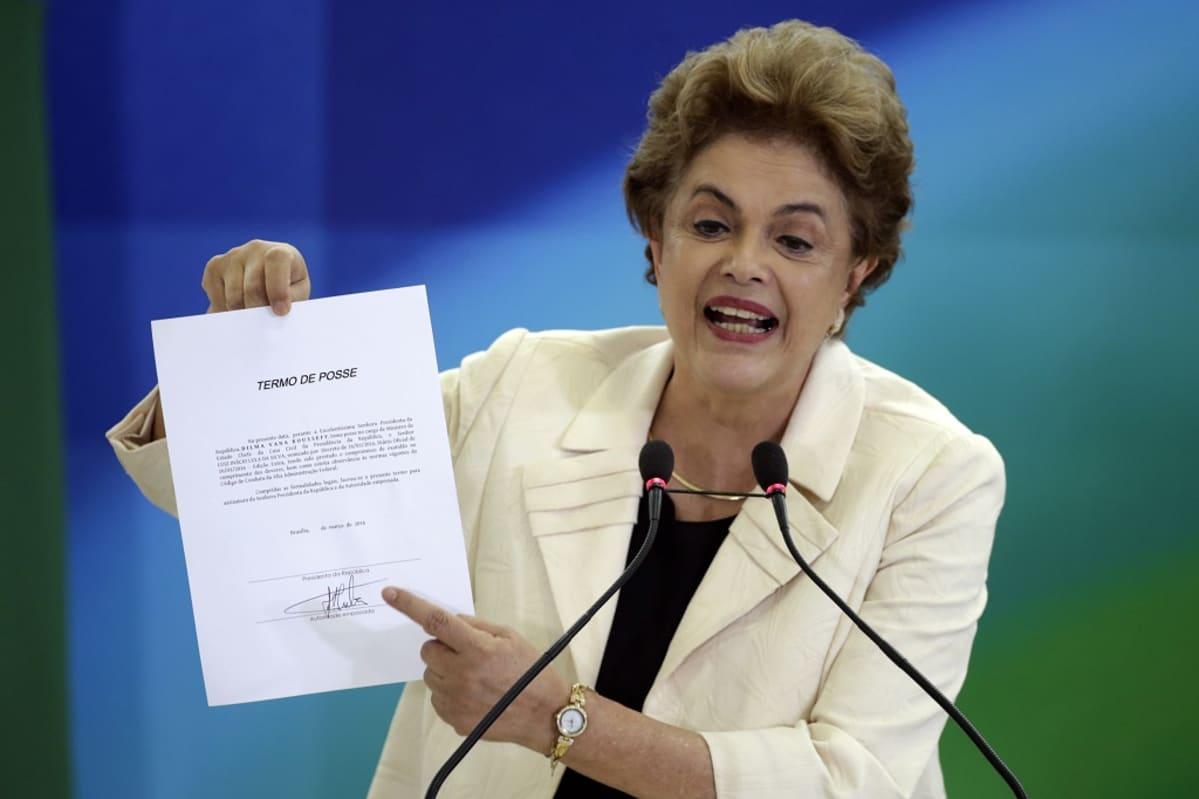 Kuvassa Dilma Rousseff puhuu kahteen mikrofoniin, pitelee oikeassa kädessään asiakirjaa ja osoittaa asiakirjassa olevaa nimikirjoitusta vasemman kätensä etusormella.