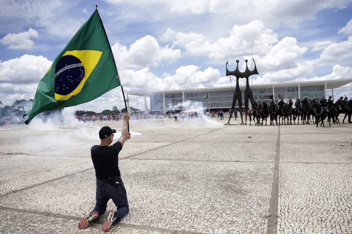 Brasilian lippua pitelevä lippalakkipäinen mies on polvillaan aukiolla ja katsoo mustanpuhuvaa rivistöä ratsupoliiseja, joka levittäytyy kahta tyylitellysti kuvattua ihmishahmoa esittävästä patsaasta vasemmalle. Kentällä leviää kyynelkaasua. Taustalla näkyy modernistinen rakennus.