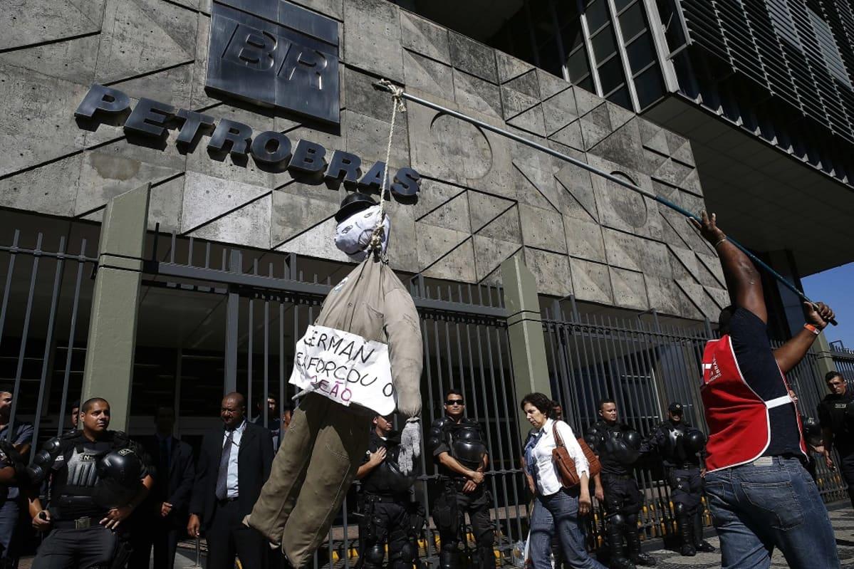 Mielenosoittaja kuljettaa kepin päähän hirtettyä nukkea Petrobrasin harmaan, modernistisen päämajan edustalla. Rakennuksen metallisen aidan edustalla seisoo poliiseja mellakkavarusteissa, kypärät ripustettuina varusteliiveihin.