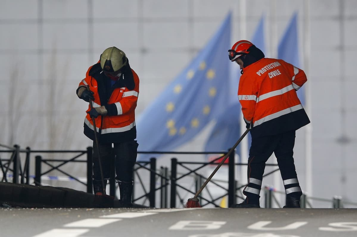 Kaksi suojatakkista ja kypäräpäistä miestä lakaisee lasinsiruja kadulta. Taustalla liehuu EU:n lippuja.