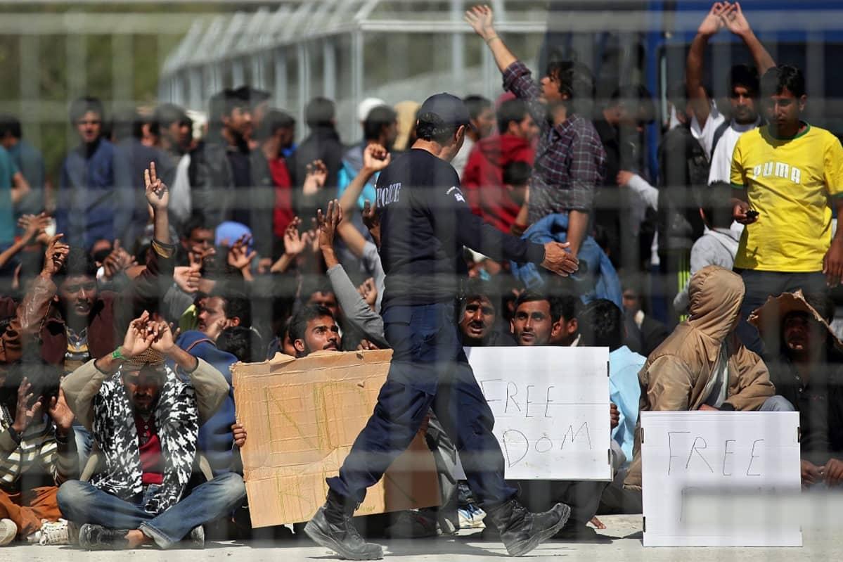 Joukko maassa istuvia ihmisiä aidan takana vapautta vaativien kylttien kanssa; etualalla vartijalta vaikuttava henkilö.