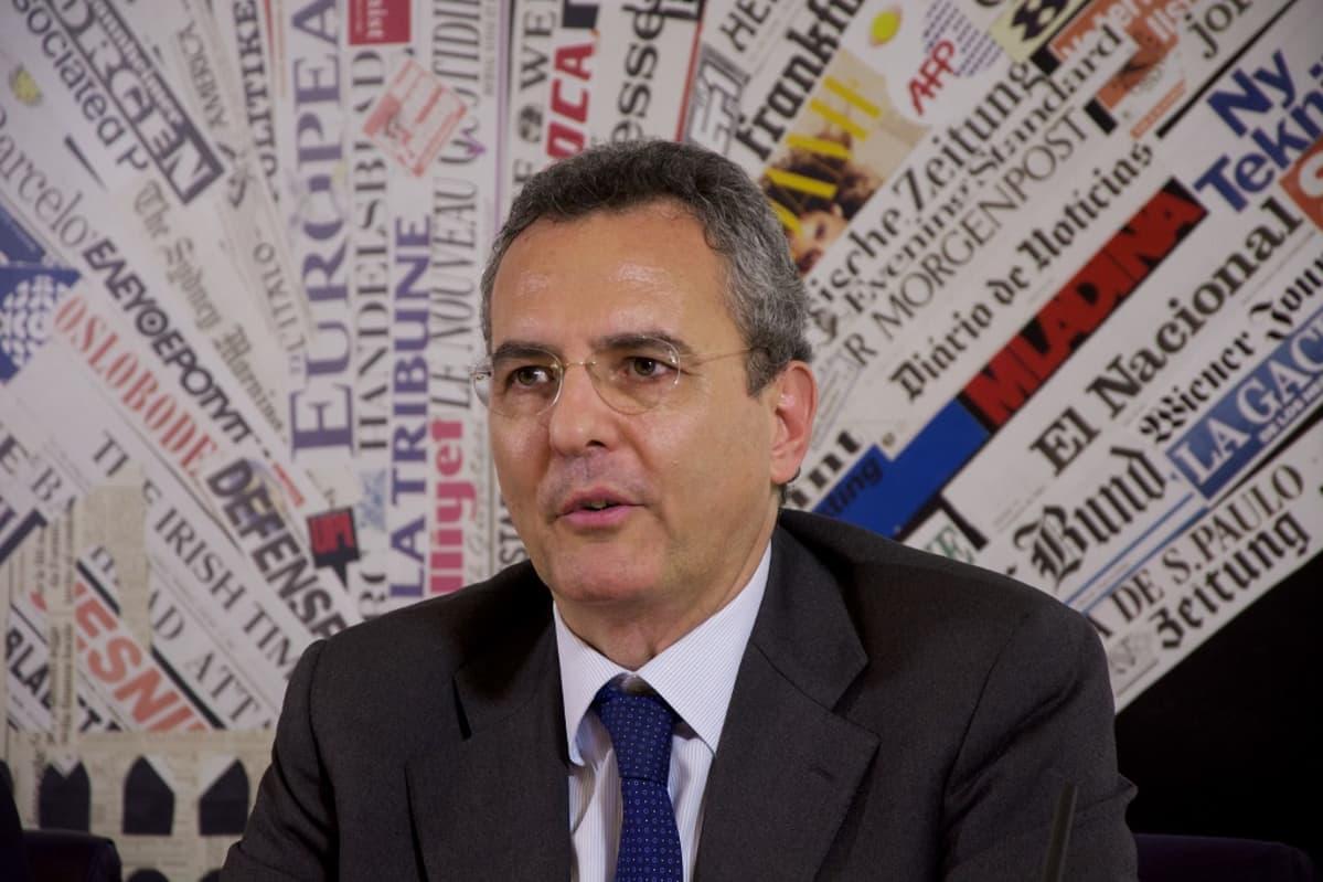 Marco Impagliazzon taustalla on viuhkaksi aseteltuja eurooppalaisten sanomalehtien sivuja.