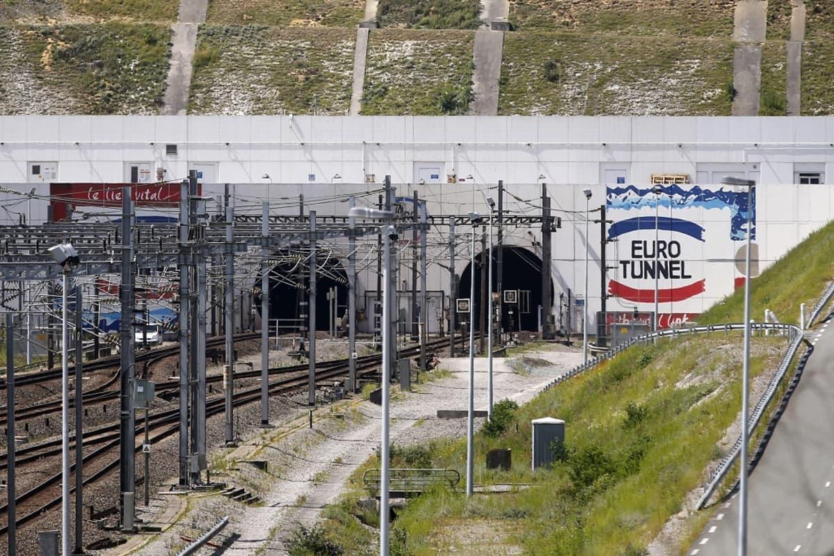 """Betonitunneliin johtavat junakiskot. Seinässä lukee """"Eurotunnel"""""""
