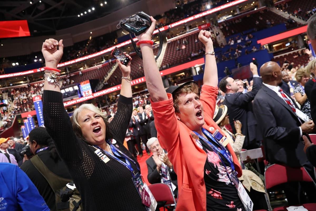 Kaksi naista iloitsee kädet ylhäällä, taustalla näkyy väkijoukkoa ja stadionin sisätiloja.