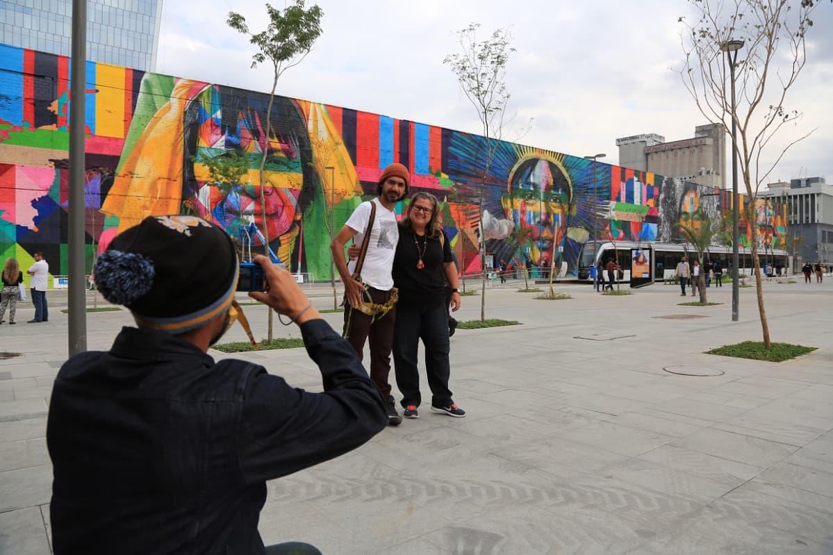 Taustalla muuriin maalattu, värikäs graffiti. Etualalla mies ottaa kuvaa muurin edessä seisovasta naisesta ja miehestä.
